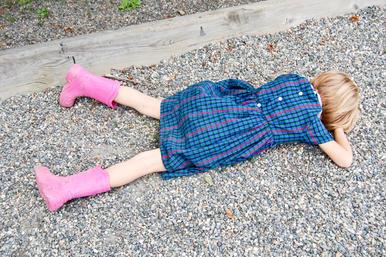 A sad child lies on the gravel of a school playground.